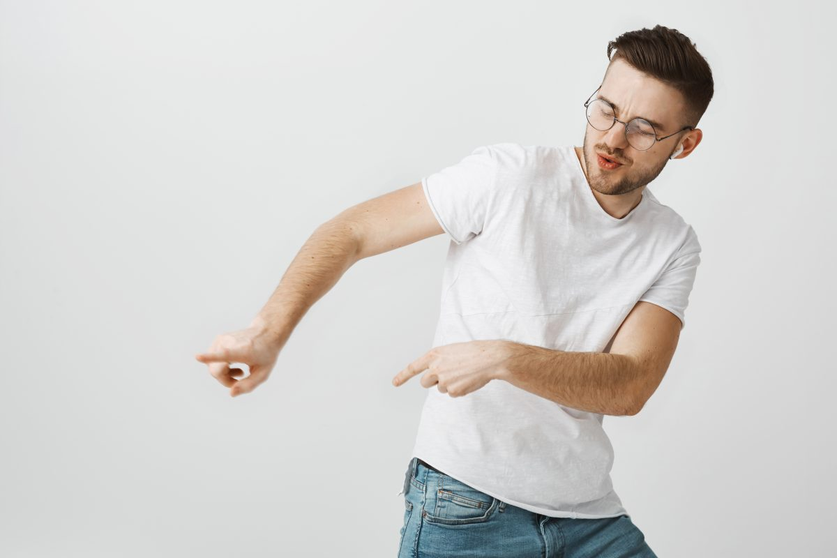 Energetic satisfied handsome young european male in casual white t-shirt dancing tilting right and making moves to rhythm of song listening music and enjoying great sound quality in wireless earphones.